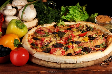 delicious pizza, vegetables and spices on wooden table on brown background photo