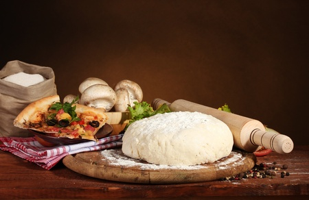 dough: delicious pizza dough, spices and vegetables on wooden table on brown background