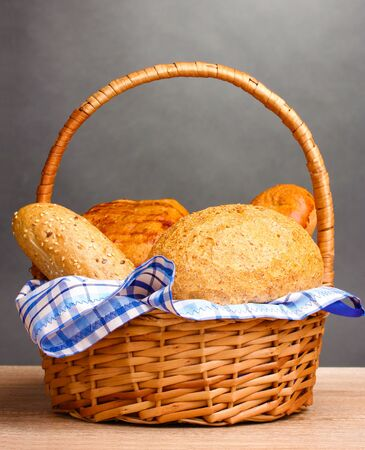 delicious bread in basket on wooden table on gray background Stock Photo - 11192866