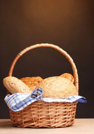 delicious bread in basket on wooden table on brown background photo