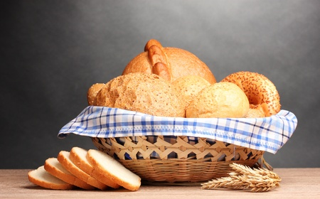 delicious bread in basket and ears on wooden table on gray background Stock Photo - 11192900