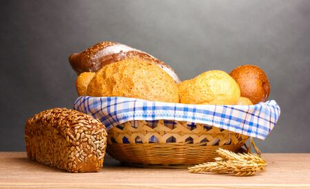 delicious bread in basket and ears on wooden table on gray background photo