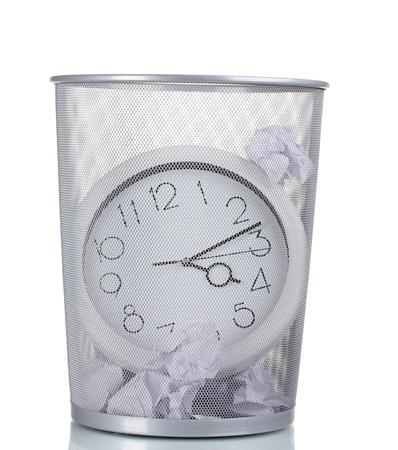 waste paper: Reloj de pared en el recipiente met�lico de basura y papel aislado en blanco