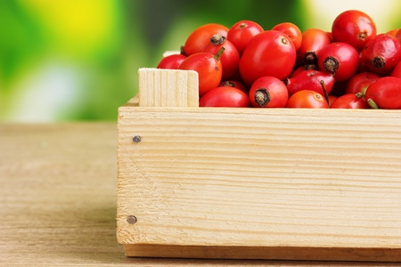 ripe briar in wooden box on wooden table on green background Stock Photo - 11195239