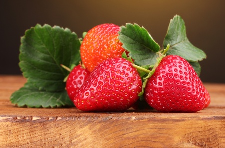 Strawberries with leaves on wooden table on brown  background photo
