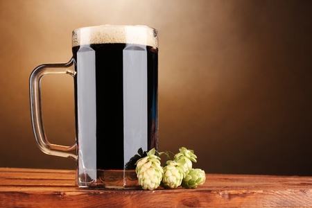 dark beer in a mug and green hop on wooden table on brown background photo