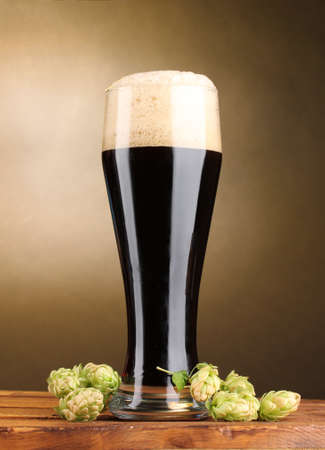 dark beer in glass and green hop on wooden table on brown background photo