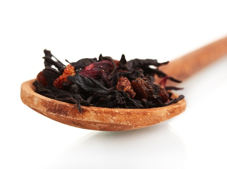 Black fruit dry tea leaves in woooden spoon isolated on white photo