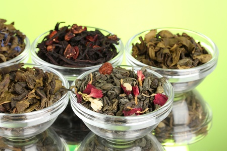 Different kinds of green and black dry tea on green background photo