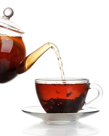 Glas Teekanne gießt schwarzen Tee in die Tasse isoliert auf weiß