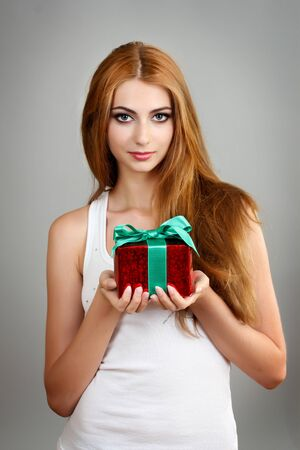 Beautiful young girl with present box on gray background photo