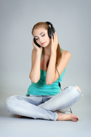 beautiful young girl in headphones with a laptop on a gray background photo