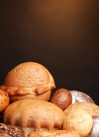 delicious bread on wooden table on brown background photo