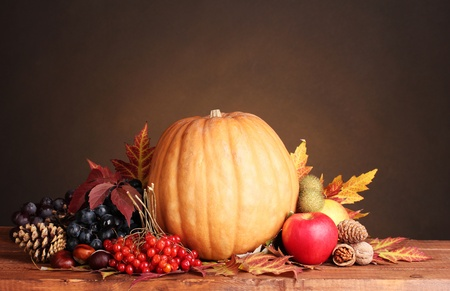 pumpkin, apples,berries and leaves on wooden table on brown background photo