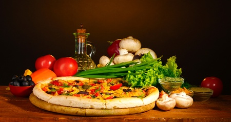 italian sausage: delicious pizza, vegetables and spices on wooden table on brown background