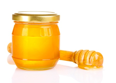 Jar of honey and wooden drizzler isolated on white photo