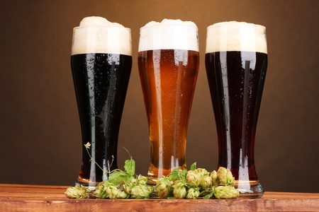 beer pint: three glasses with different beers and hop on wooden table on brown background