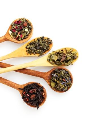 frutas secas: Diversas clases de t� seco verde y negro en cuchara woooden aislado en blanco