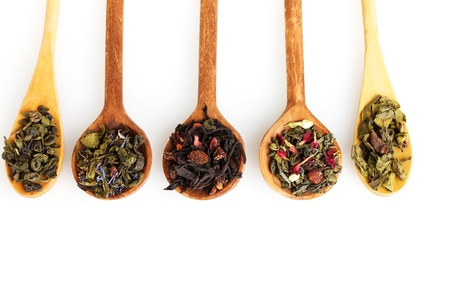 Different kinds of green and black dry tea in woooden spoon isolated on white
