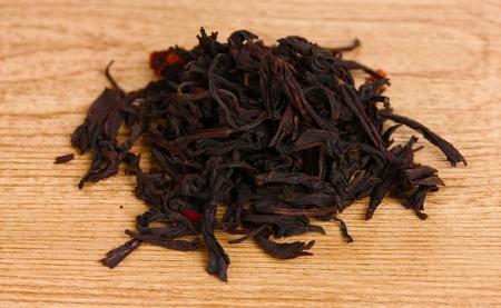 Black dry tea on wooden table photo