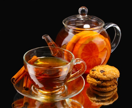 Glass teapot and cup with black fruit tea and cookies isolated on white photo