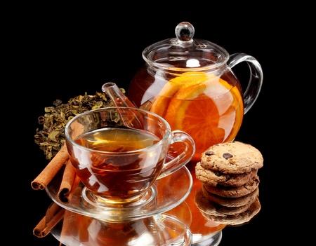 Glas Teekanne und Tasse mit schwarzen Früchten Tee und Gebäck isoliert auf weiß