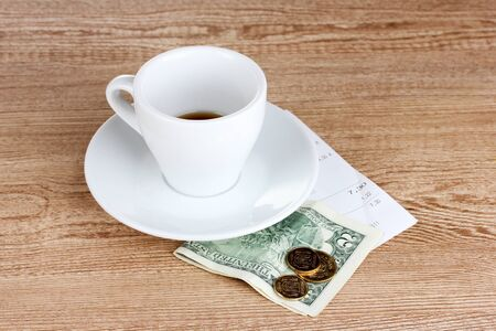 Empty cup of coffee with five dollars tip on wooden background photo