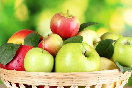 Fresh organic apples in basket on wooden table outside photo