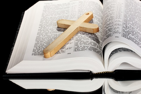 Russian bible and wooden cross on black background Stock Photo - 11417851