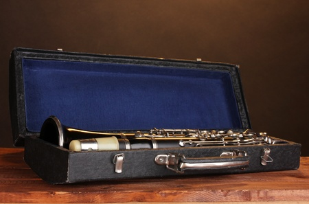 old clarinet in case on wooden table on brown background photo