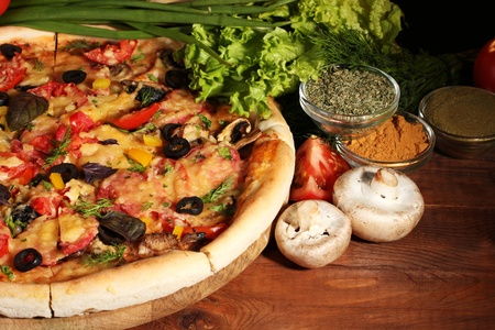 delicious pizza, vegetables and spices on wooden table Stock Photo - 11399575