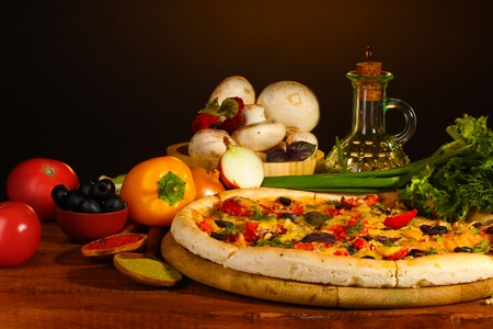 delicious pizza, vegetables and spices on wooden table on brown background