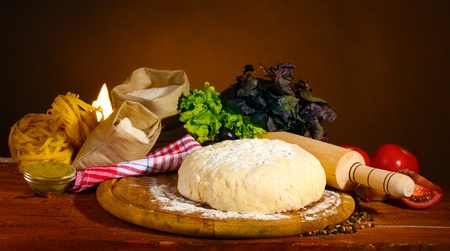 ingredients for homemade pizza on wooden table on brown background photo