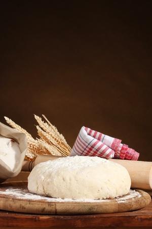 levadura: Masa y bolsas con harina en la mesa de madera sobre fondo marr�n