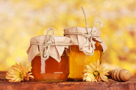 two jars of honey and wooden drizzler on table on yellow background photo