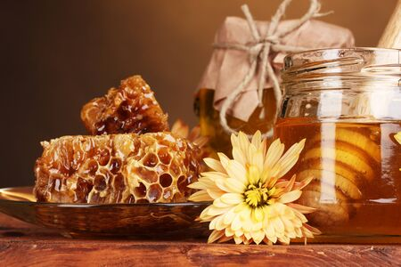 two jars of honey,honeycombs and wooden drizzler on table on yellow background Stock Photo - 11407797
