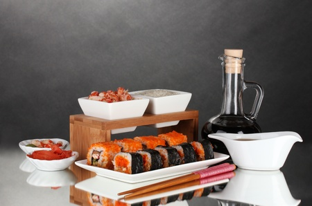 delicious sushi on plate, chopsticks, soy sauce, fish and shrimps on gray background photo