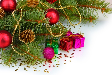 Green Christmas tree with gift, toy and cones isolated on white photo