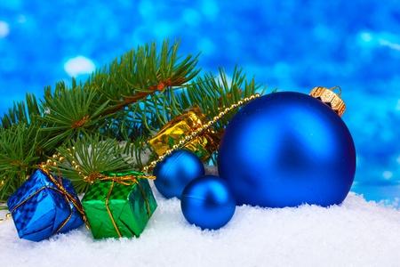 Kerst bal en speelgoed met groene boom in de sneeuw op blauw