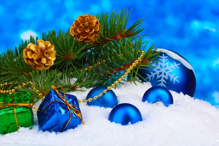 Christmas ball and green tree in the snow on blue photo