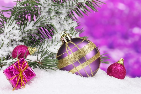 christmas tree purple: Christmas ball and toy with green tree in the snow on purple Stock Photo