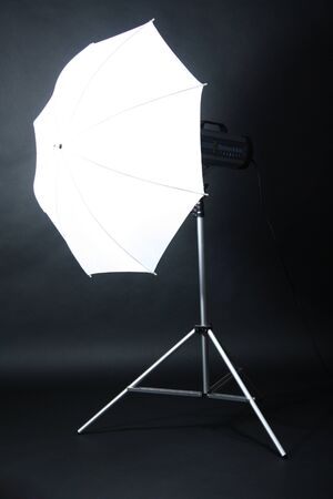 Studio flash with umbrella on grey background photo