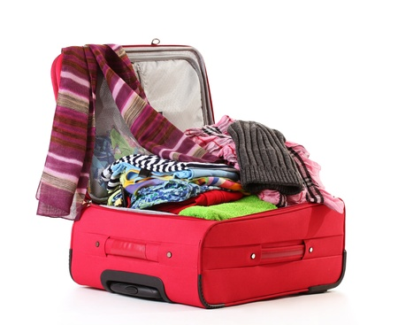 Open red suitcase with clothing isolated on white photo