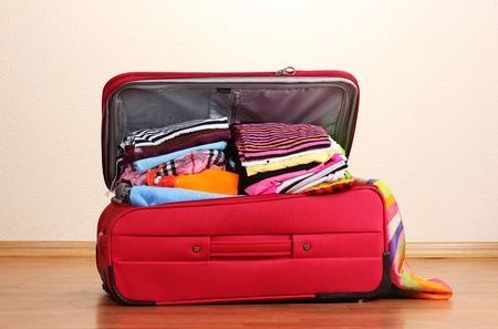 open suitcase: Open red suitcase with clothing in the room