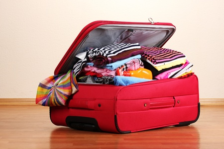 Open red suitcase with clothing in the room photo