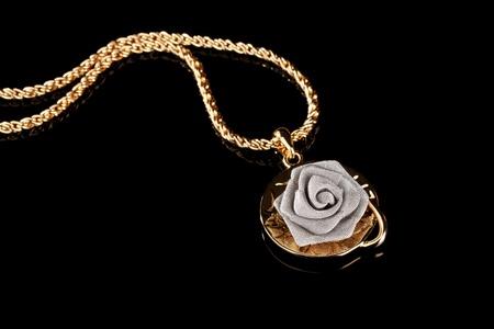 Pendant in form of rose on black Reklamní fotografie - 11417963
