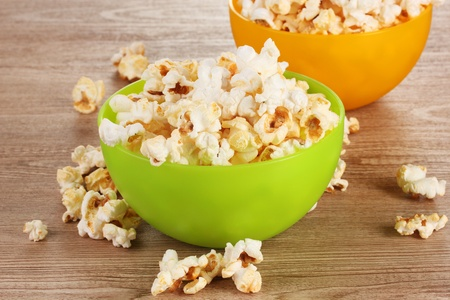 popcorn in bright plastic bowls on wooden table photo