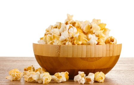 popcorn in wooden bowl on wooden table on white background photo