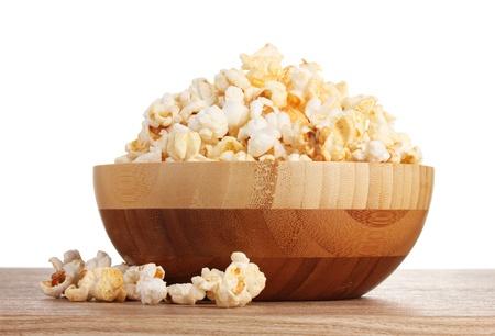 popcorn in ciotola di legno su tavola di legno su sfondo bianco