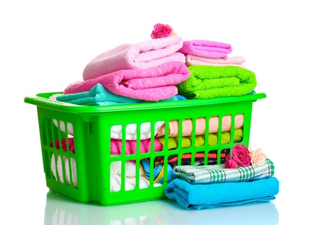 detergents: Towels in green plastic basket isolated on white